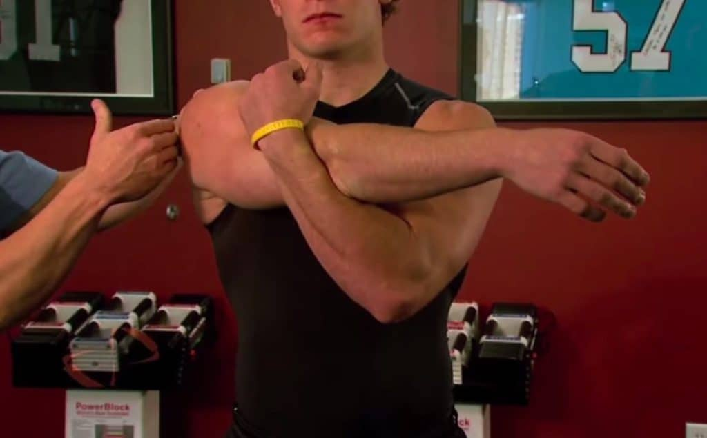 man doing cross arm stretches