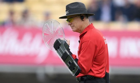 Cricket Umpire Bruce Oxford wearing a shield like device on his arm known as the arm guard to protect his head