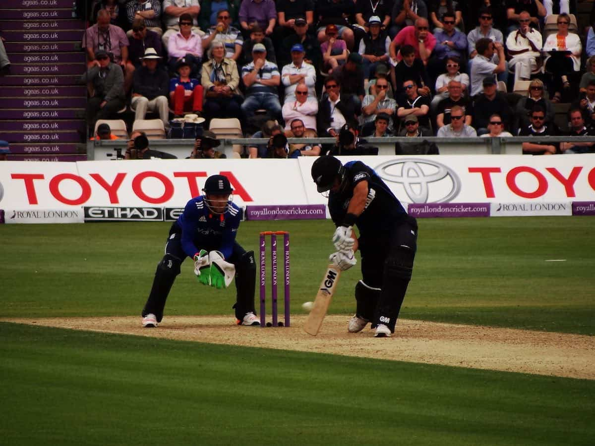 A cricket batsman plays a shot while the wicketkeeper looks on.