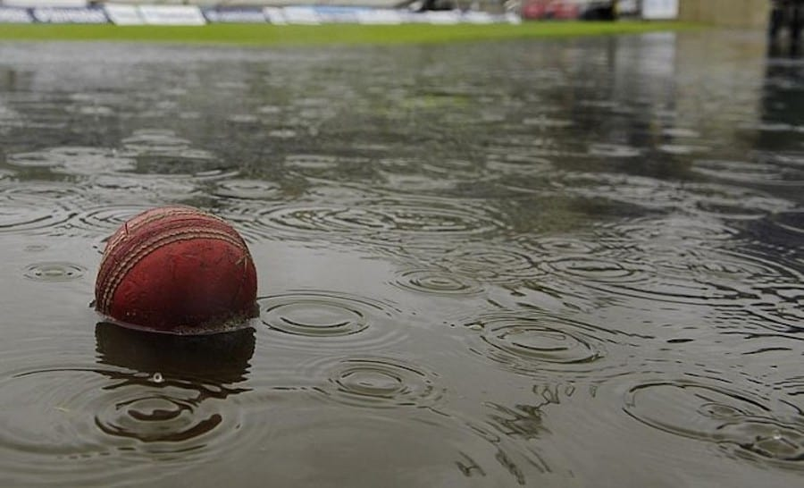A cricket ball in the puddle of water on the cricket ground